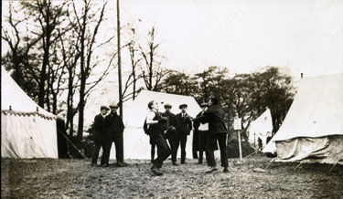 Two new recruits boxing outside tents, watched by a small audience